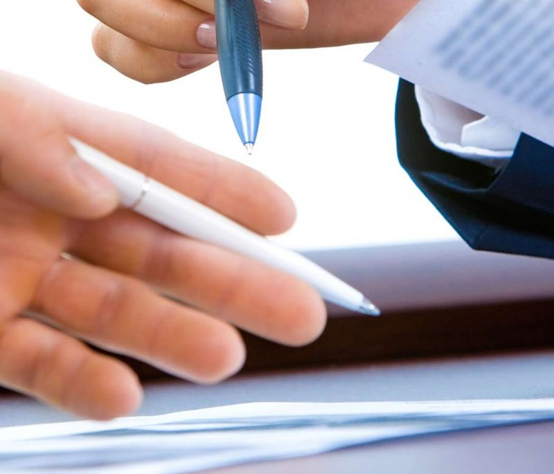 two people with pen and paper in hands reviewing documents